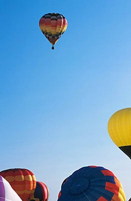 View of hot air balloons from the ground uid 1183463